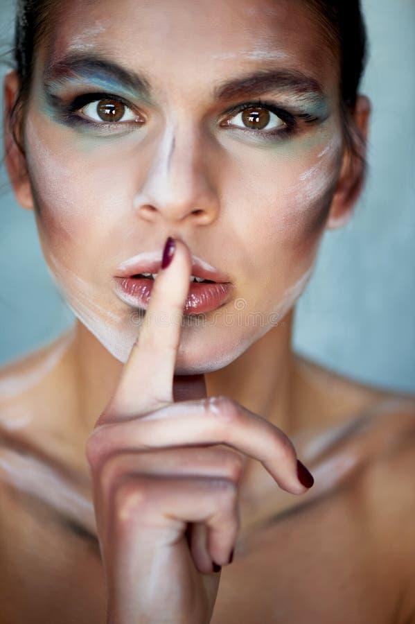 Personalidad creativa con el maquillaje, manchas de la pintura en la cara Él pone su finger a sus labios Firme Shh imagenes de archivo