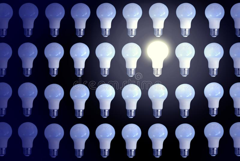 Personality among the crowd. Concept with one switched on lighting bulb among switched off bulbs. Not like everyone else idea royalty free stock photo