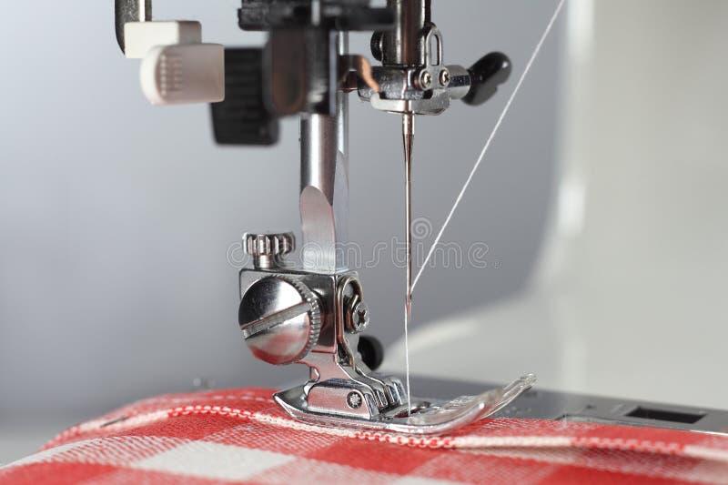 personalizaci?n Parte operante de la máquina de coser con la tela de lino en el glóbulo rojo fotos de archivo