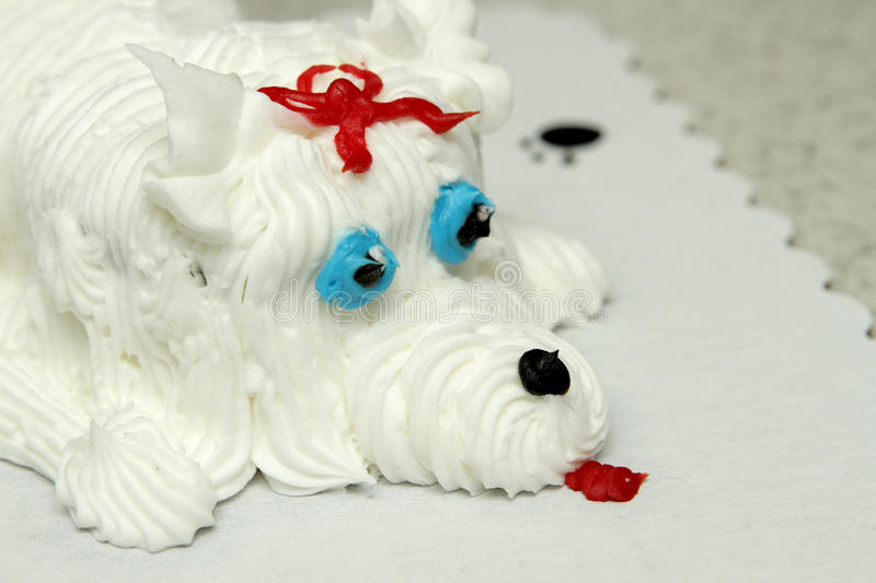 Personalized birthday cake dog. Closeup of the face of a birthday cake in the shape of a dog royalty free stock images