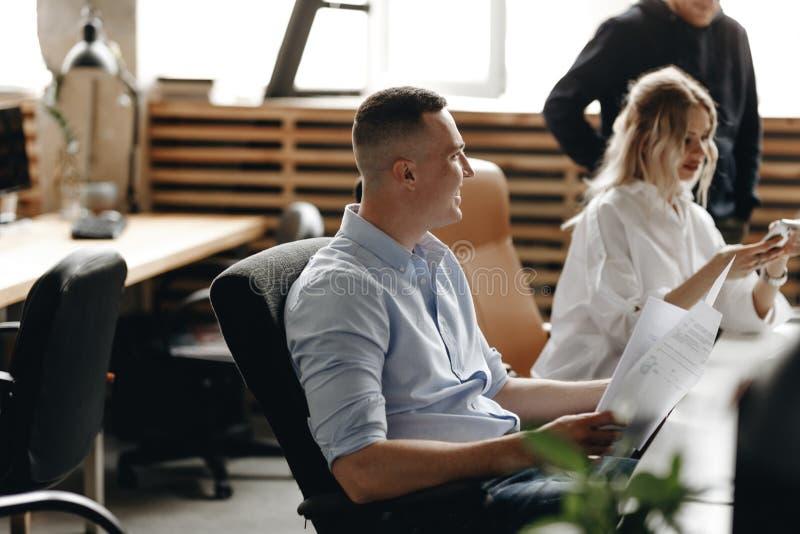 Personalmöte av ett ungt lyckat lag ett ljust modernt kontor som utrustas med modern kontorsutrustning royaltyfria bilder