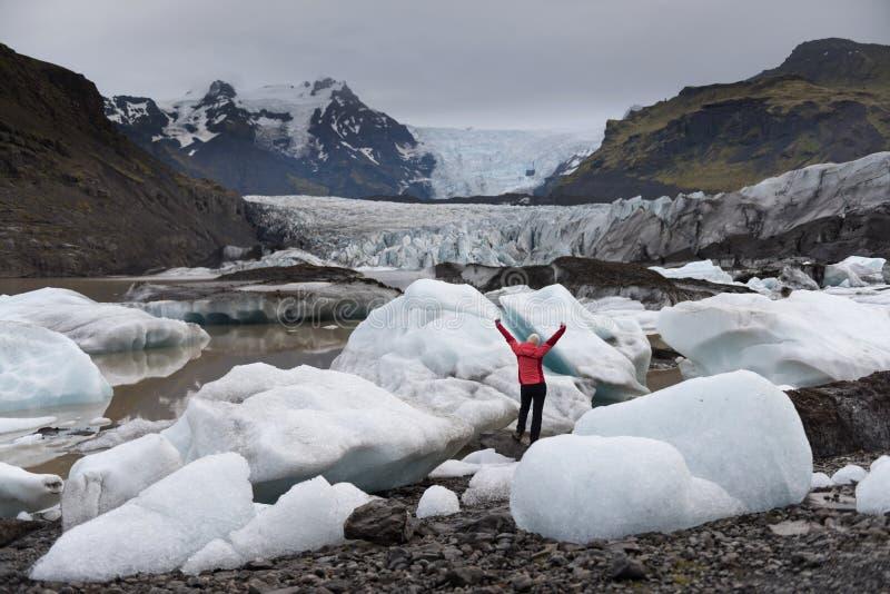 personanseendet vaggar på med lyftta händer och att se sceniskt icelandic landskap royaltyfri foto