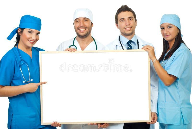 Personas de doctores con la bandera en blanco imagen de archivo