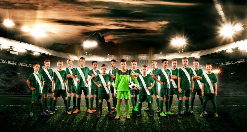 Personas de fútbol Niños - campeones futuros Muchachos en ropa de deportes del fútbol en estadio con la bola Concepto del deporte foto de archivo libre de regalías