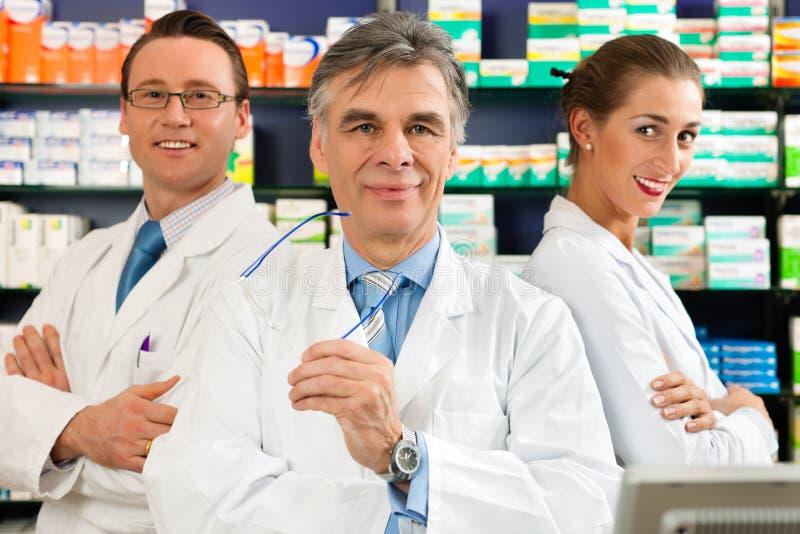 Personas de farmacéuticos en farmacia foto de archivo libre de regalías