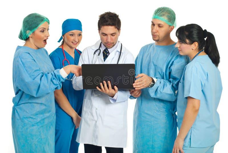 Personas de la búsqueda de los doctores en la computadora portátil fotografía de archivo
