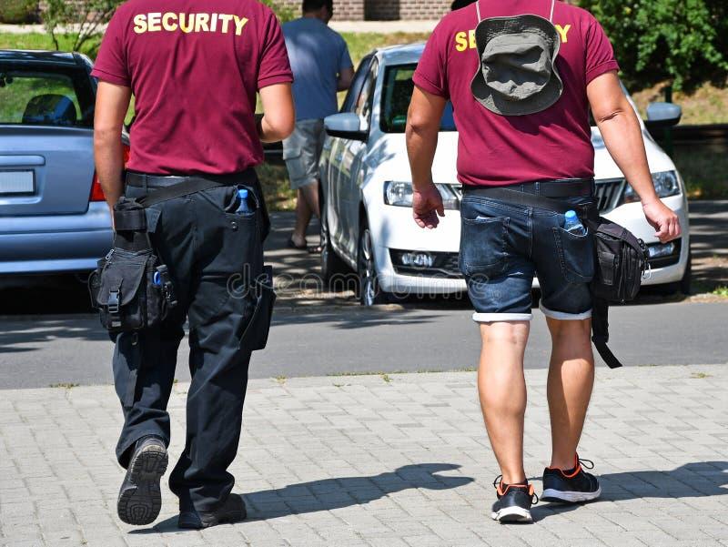 Personas de la seguridad al lado de un estacionamiento imagenes de archivo