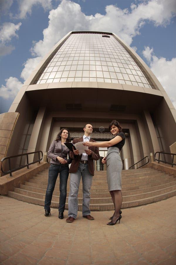Personas del asunto delante de un edificio fotografía de archivo