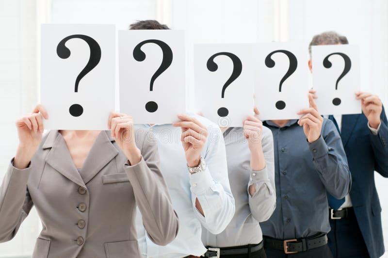 Personas del asunto detrás de signos de interrogación foto de archivo libre de regalías