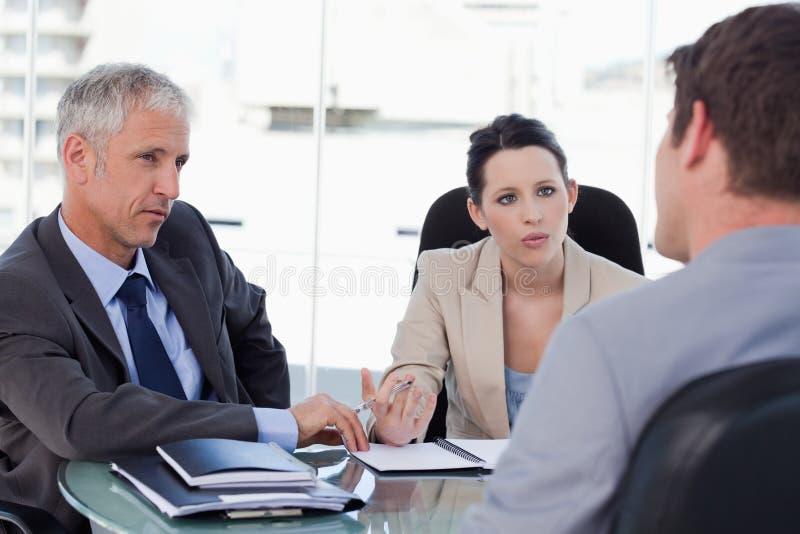 Personas del asunto que negocian con un cliente fotografía de archivo libre de regalías
