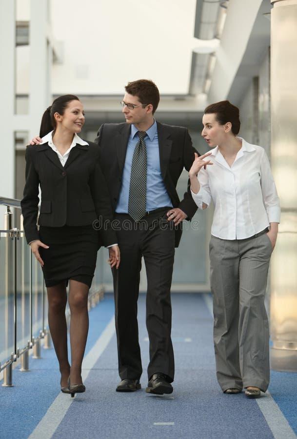 Personas del grupo tres que hablan la oficina que recorre imagen de archivo