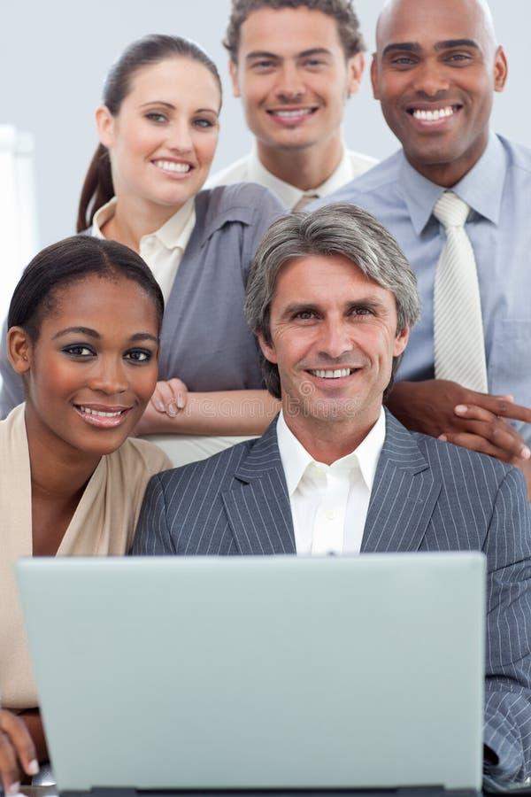 Personas diversas del asunto que trabajan en una computadora portátil fotos de archivo