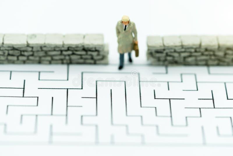 Personas en miniatura: Empresario caminando a la pared en laberinto Conceptos de búsqueda de una solución, solución de problemas  foto de archivo