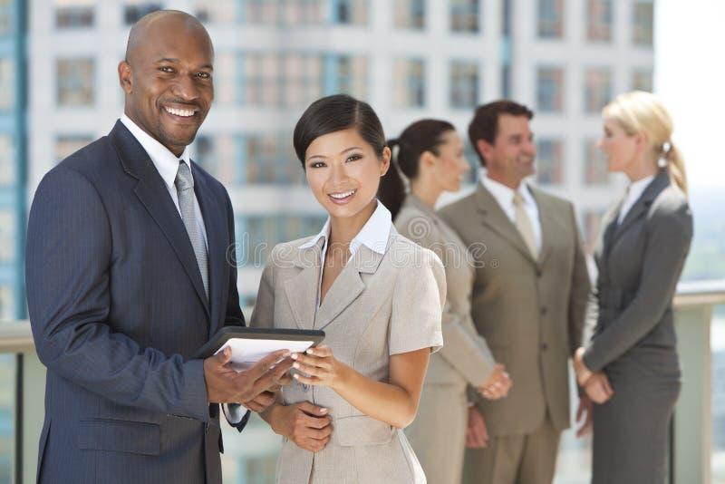 Personas interraciales del asunto con el ordenador de la tablilla imagenes de archivo