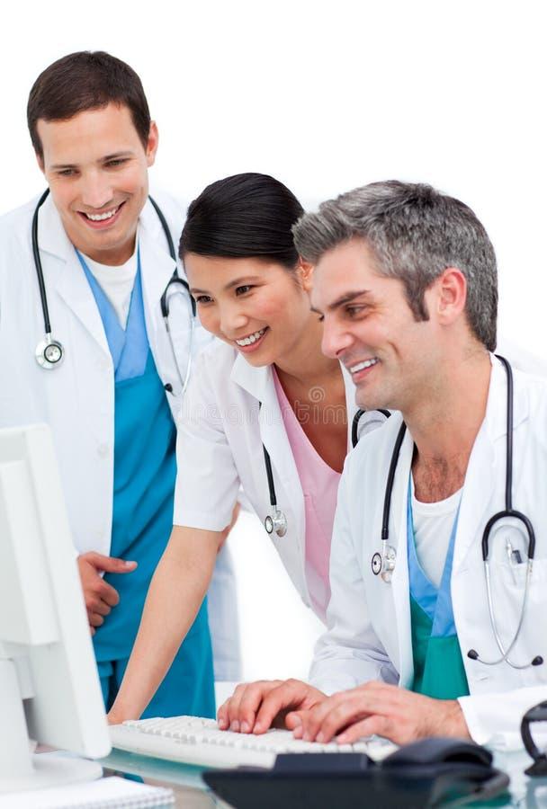 Personas médicas alegres que trabajan en un ordenador foto de archivo