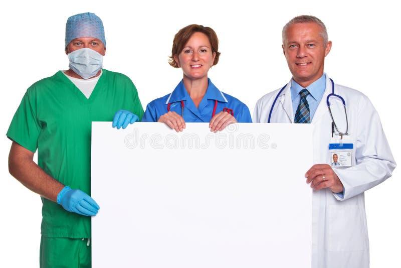 Personas médicas que sostienen un cartel en blanco aislado foto de archivo