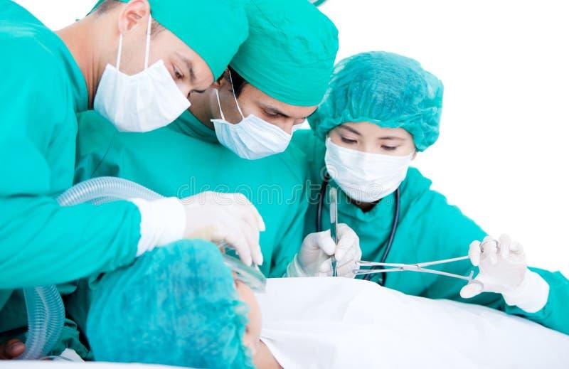 Personas médicas usando el equipo de la cirugía fotografía de archivo