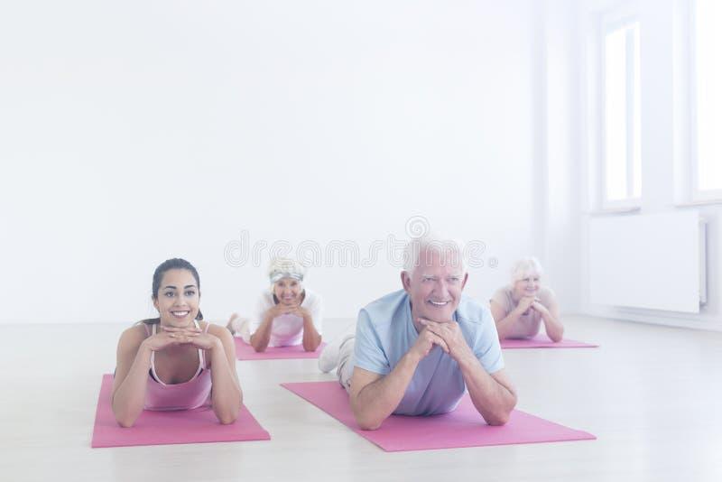 Personas mayores que mienten en las esteras imagenes de archivo