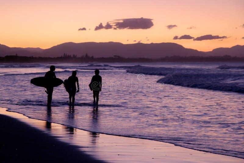 Personas que practica surf que caminan en la playa durante la puesta del sol fotos de archivo libres de regalías