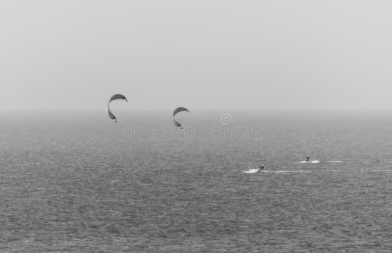 Personas que practica surf de la cometa en Northumberland blanco y negro fotos de archivo