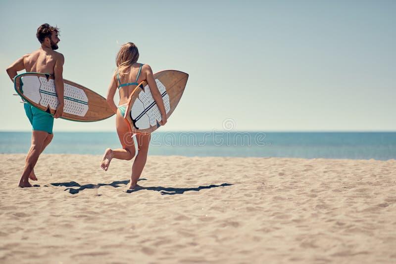 Personas que practica surf del hombre y de la mujer que corren junto para practicar surf en la playa imagenes de archivo