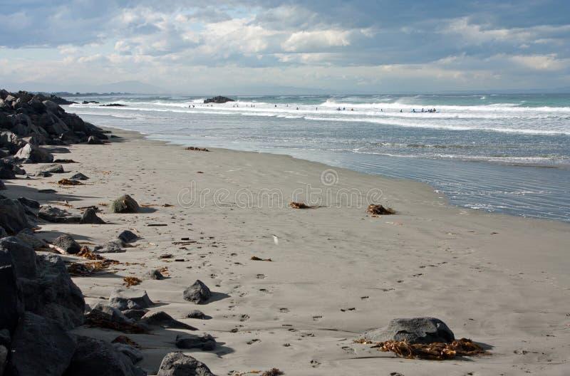 Personas que practica surf en el mar ondulado en Sumner Beach en Christchurch en Nueva Zelanda fotografía de archivo libre de regalías