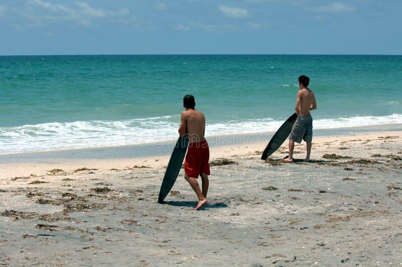 Personas que practica surf en la playa imagenes de archivo