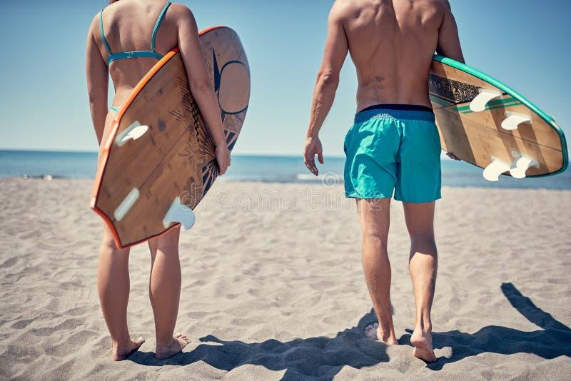 Personas que practica surf en la playa - hombre y mujer atractivos en la playa fotos de archivo libres de regalías