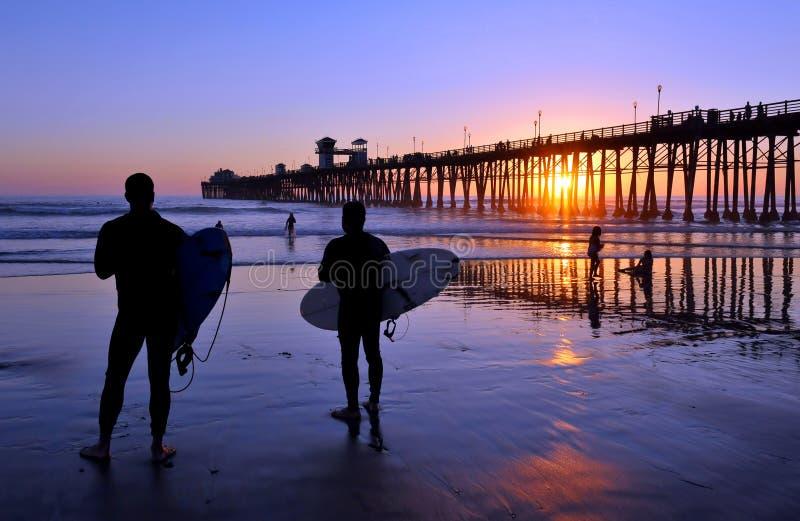 Personas que practica surf en la puesta del sol foto de archivo libre de regalías