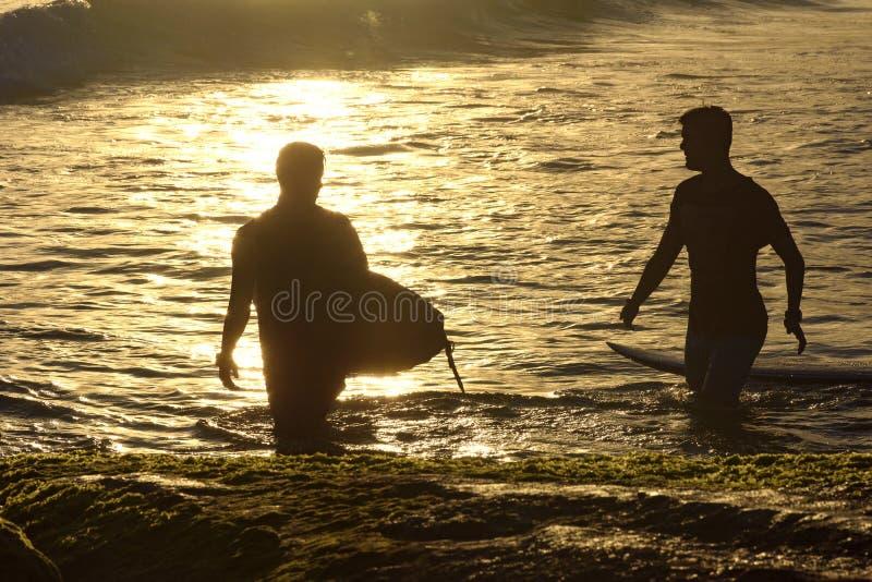 Personas que practica surf en la puesta del sol imagen de archivo
