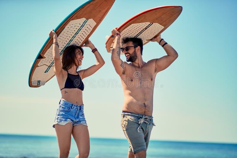 Personas que practica surf en los pares jovenes de la playa de las personas que practica surf que caminan en el bea fotos de archivo