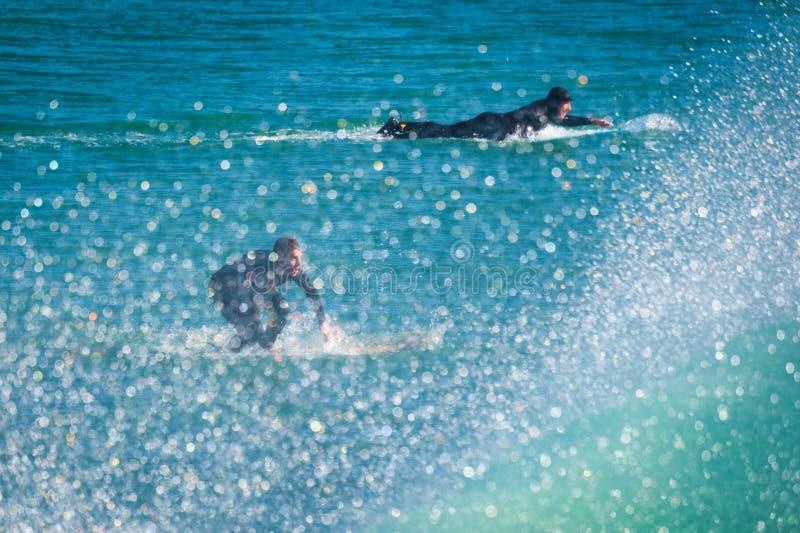 Personas que practica surf y espray de ondas fotos de archivo libres de regalías