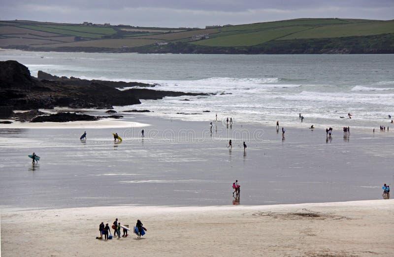 Personas que practica surf y nadadores en la playa foto de archivo