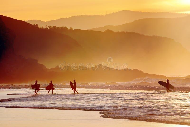 Personas que practica surf y tableros de la boogie en la puesta del sol imagen de archivo