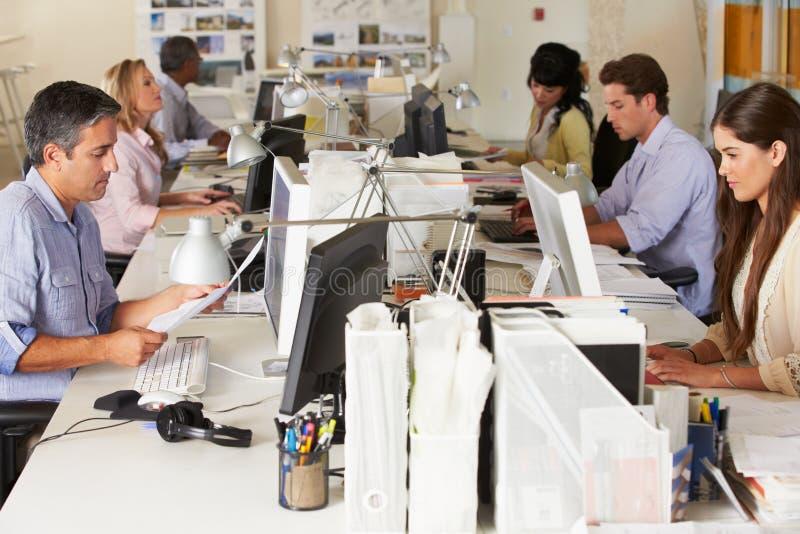 Personas que trabajan en los escritorios en oficina ocupada imagen de archivo