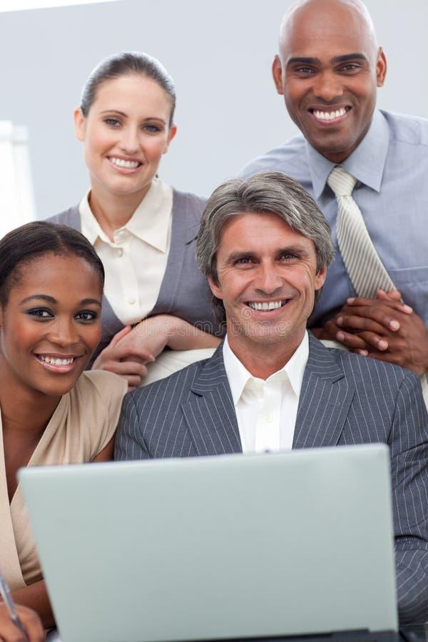 Personas sonrientes del asunto que trabajan en una computadora portátil fotos de archivo libres de regalías
