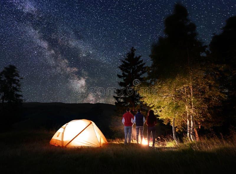 Personblick för bakre sikt tre på den brinnande branden nära tältet och träd under den ovanliga stjärnklara himlen royaltyfri fotografi