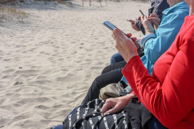 Persone anziane che si siedono su un banco alla spiaggia ed agli smartphones di uso fotografia stock