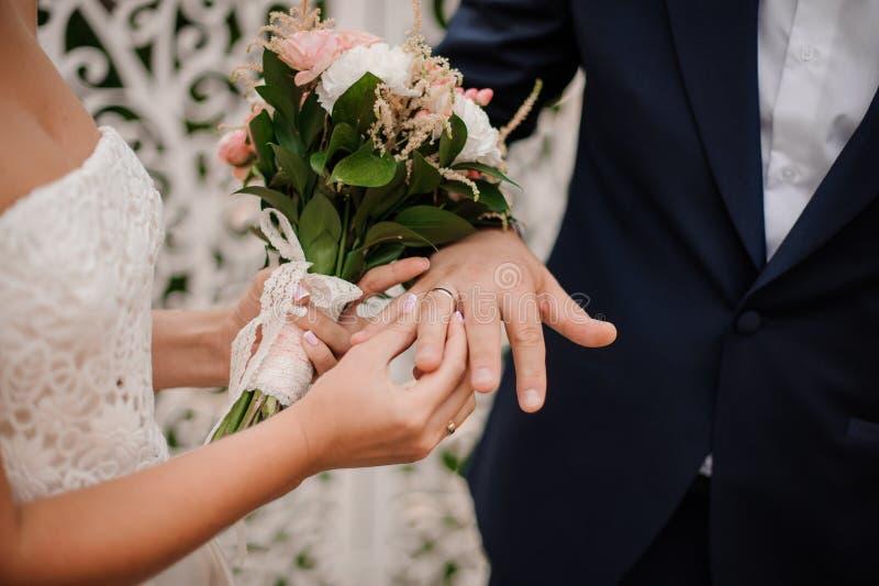 Persone appena sposate che scambiano gli anelli, sposa che mette l'anello sulla mano del ` s dello sposo fotografie stock libere da diritti