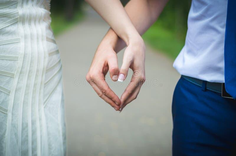 Persone appena sposate che si tengono per mano sotto forma di un cuore fotografia stock