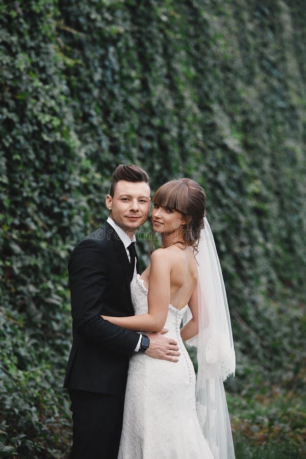 Persone appena sposate delle coppie, supporti dello sposo e della sposa e mazzo felici di tenuta dei fiori e dei verdi nel giardi fotografie stock libere da diritti