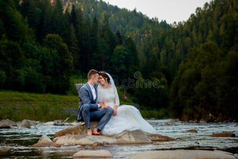 Persone appena sposate felici che stanno e che sorridono sul fiume Honeymooners, foto per il San Valentino fotografia stock