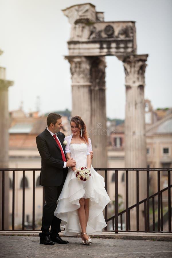 Persone appena sposate nella città antica Coppia sposata felice Belle vecchie finestre a Roma (Italia) immagine stock