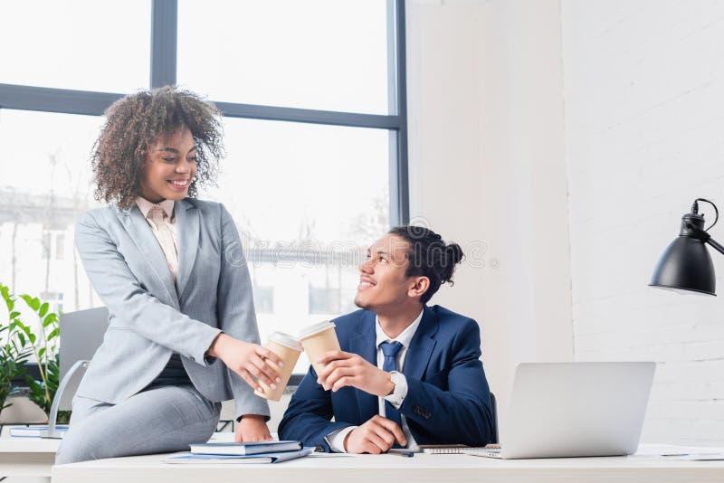 Persone di affari afroamericane che tostano con le tazze di carta immagini stock