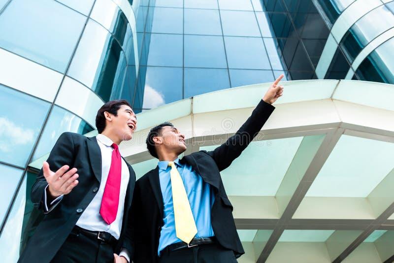 Persone di affari asiatiche davanti a grattacielo fotografia stock