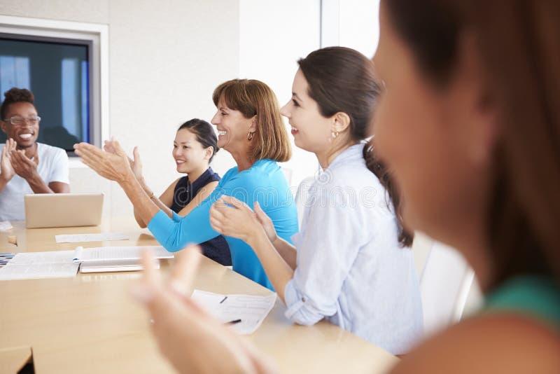 Persone di affari che applaudono collega in sala del consiglio fotografie stock