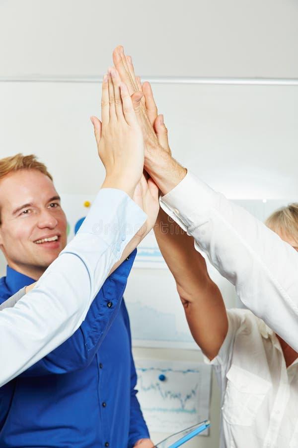 Persone di affari che applaudono le mani per dare livello cinque fotografia stock