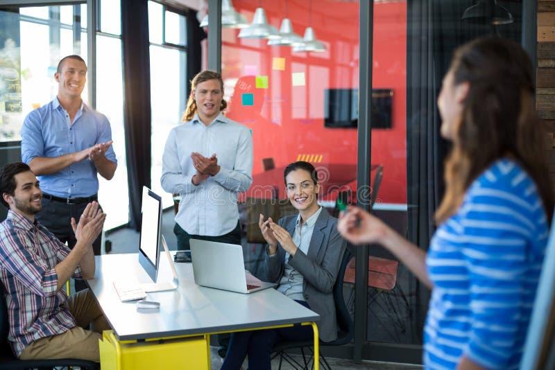 Persone di affari che apprezzano il loro collega durante la presentazione fotografia stock libera da diritti