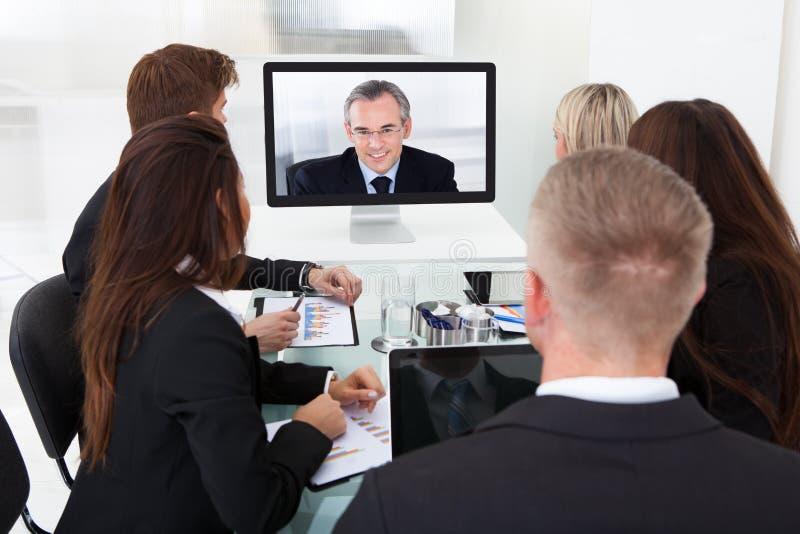 Persone di affari che assistono alla videoconferenza immagine stock