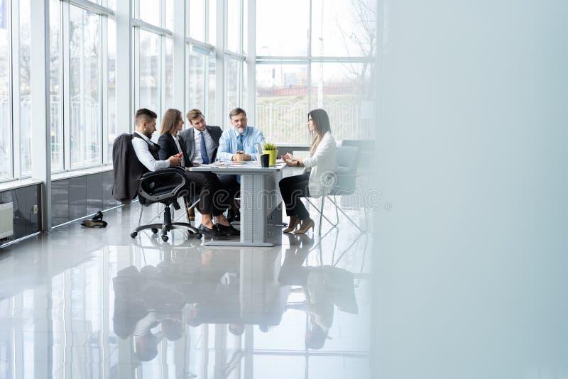 Persone di affari che discutono insieme nell'auditorium nel corso della riunione all'ufficio immagini stock libere da diritti